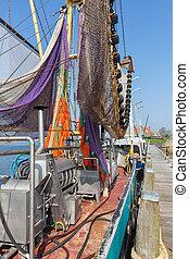 Harbor dutch fishing village Makkum with shrimp trawler drying nets