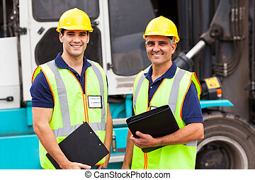 warehouse worker standing in front of container forklift - ...