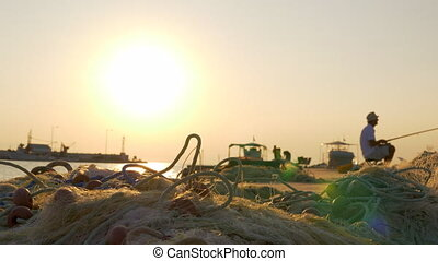 Harbor with fisherman and fishing nets on the pier. Sunset...