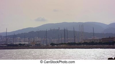 Harbor with sailing ships and the old Bellver Castle on the background in Palma de Mallorca, Spain