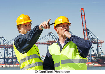 Harbor workers - Two dockers in discussion, in front of a...
