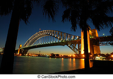 Harbour Bridge in Sydney, sunset, reflection in water, palm silhouette in foreground