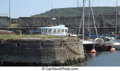 Harbour with boats docked in Irish town - A panning shot of...