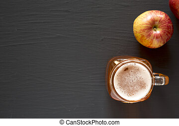 Hard Apple Cider Ale in a Glass Jar Mug on a black background, top view. Flat lay, overhead, from above. Copy space.