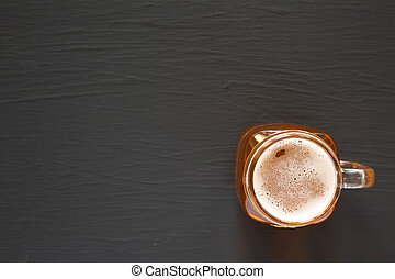 Hard Apple Cider Ale in a Glass Jar Mug on a black surface, top view. Flat lay, overhead, from above. Copy space.