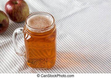Hard Apple Cider Ale in a Glass Jar Mug on cloth, low angle view. Space for text.