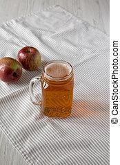 Hard Apple Cider Ale in a Glass Jar Mug on cloth, low angle view.