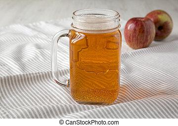 Hard Apple Cider Ale in a Glass Jar Mug on cloth, side view. Close-up.