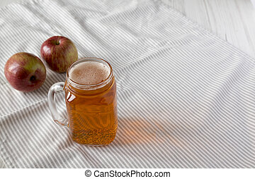 Hard Apple Cider Ale in a Glass Jar Mug on cloth, side view. Copy space.