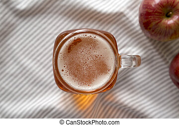 Hard Apple Cider Ale in a Glass Jar Mug on cloth, top view. Flat lay, overhead, from above.