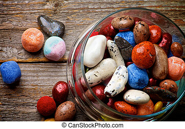 Various Colored Gum and Hard Candies in Glass Jar on Rustic Wooden background. Top View
