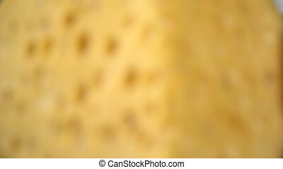 Hard cheese with holes on the cutting board