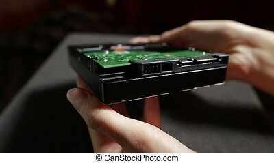 Hard disk drive close up stock footage. Female hands showing the underside of an HDD drive with connections and circuit board.