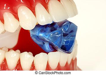 Hard Enamel - Teeth Biting Down on a Blue Stone