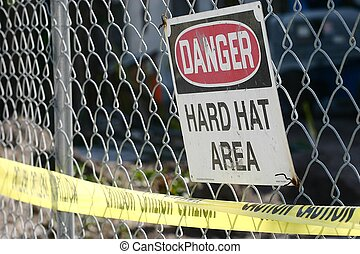 Hard Hat Area - A warning sign and a yellow caution tape on...