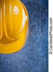 Hard hat on scratched vintage metallic background construction c