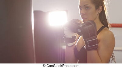 Hard hitting female boxer training in boxing club