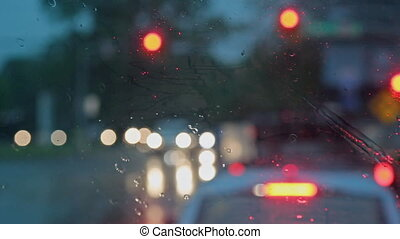 Hard rain fall at night with blurry cars selective focus. -...