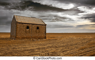Hard Times - An old farm building surrounded by dark clouds