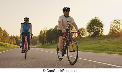 Hard Training.Triathlete two Cyclist Training On Road...