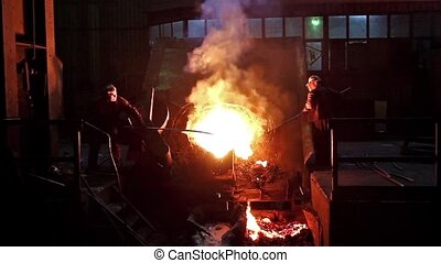 Hard work in the foundry - Workers operates in blast furnace...