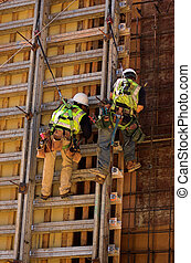 Hard Work on a High Wall - Two men working on the concrete...