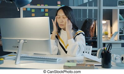 Hard-working Asian girl is working overtime in dark office touching head feeling migraine typing with computer. Technology and health concept.