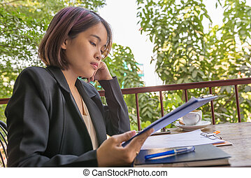 Hard-working woman in black suit reading document in garden background