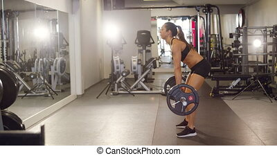 Hard working woman training deadlifts with heavy weights in...