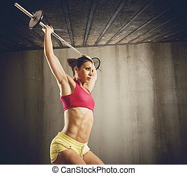 Hard workout with barbell - Muscular woman doing hard...