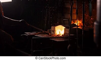 Hardening of the metal by sharp cooling in water. There is steam. The blacksmith tempers a red-hot sword on an old technology. Creation of ancient weapons. Blacksmith's Armory