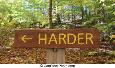 HARDER trail. Biker in background. - Sign shows the...