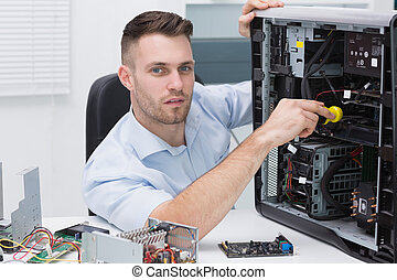 Portrait of hardware professional examining cpu with stethoscope at workplace