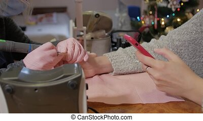 Hardware professional manicure woman hands with phone closeup