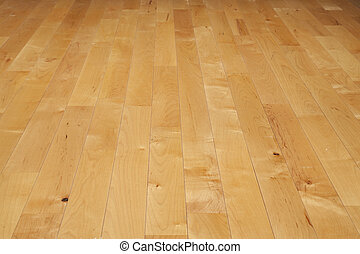 A basketball court floor made of maple hardwood viewed at a low angle
