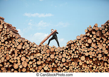 Hardworking Business Man on top of large pile of logs lifting heavy log