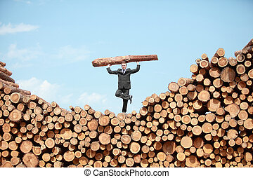 Hardworking Business Man on top of large pile of logs lifting heavy log standing on one leg - front view
