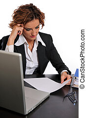 A beautiful young business woman working hard at her desk, very concentrated.