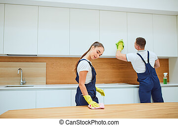 Hardworking cleaning service team at work in kitchen with white interior