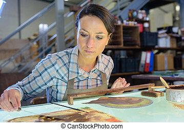 hardworking female carpenter using abrasive paper