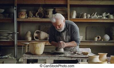 Hardworking grey-haired man is working with clay on potter's...