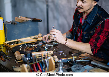 hardworking jeweler working with different pieces of metal