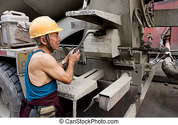 hardworking laborer and truck-concrete mixer on construction site