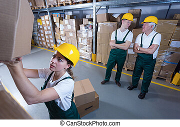Hardworking woman and lazy co-workers in warehouse