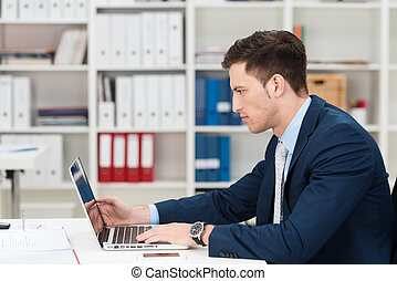 Hardworking young businessman at his desk frowning as he concentrates on information on the screen of his laptop computer, side view