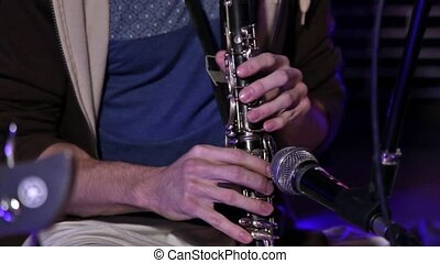 Hare Krishna Man Playing wind instrument clarinet Close-up.