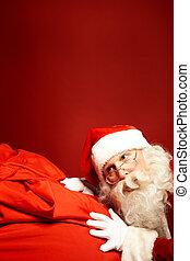 Hark - Portrait of Santa Claus leaning over huge red sack