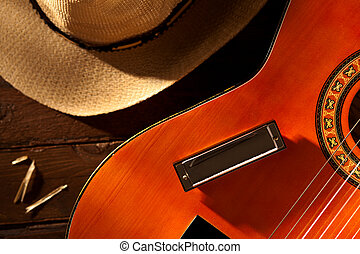 Harmonica on Guitar with Cowboy Hat on Wood