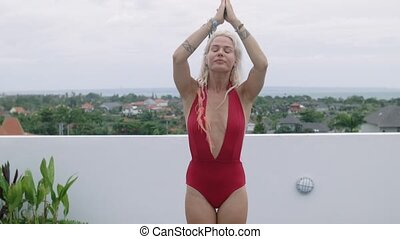 Harmonious young woman in the red bathing suit practicing yoga on the floor of the open veranda