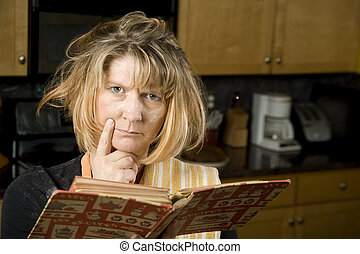 Harried woman in residential kitchen with recipe book